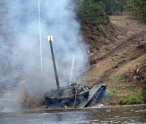Обучение подводному вождению боевых машин. Танк выходит из водной преграды с поднятой трубой ОПВТ