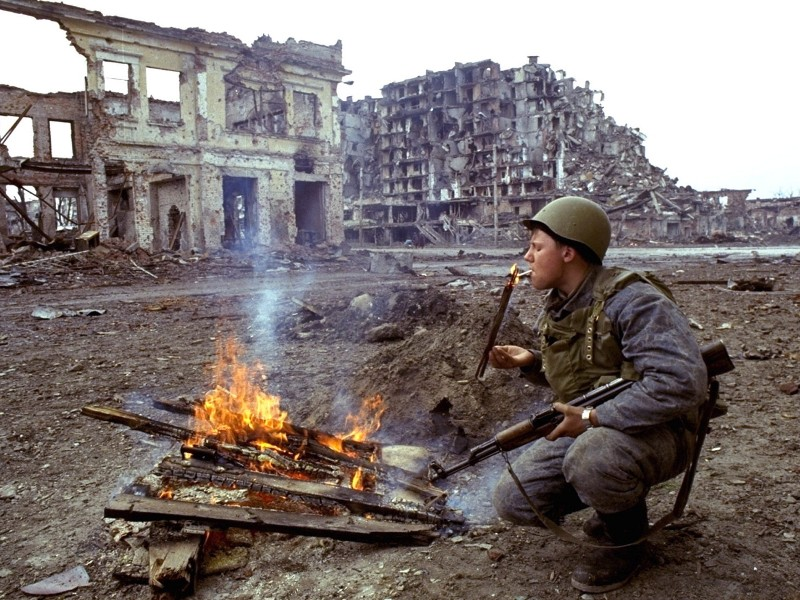 Боец прикуривает от костра. Грозный. Март 1995